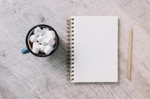 Leerer notizblock mit schale marshmallows Kostenlose Fotos