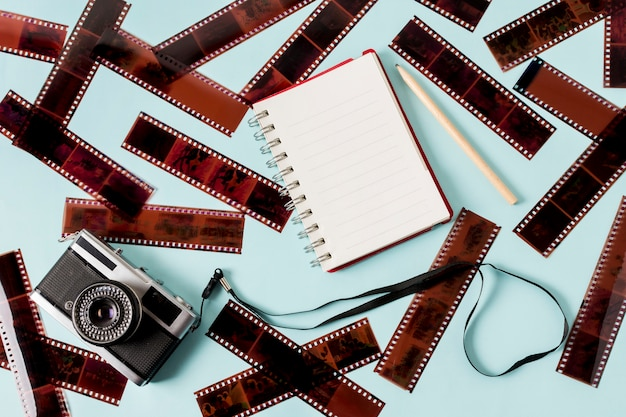 Leerer notizblock mit spirale; bleistift und kamera mit negativen streifen auf blauem hintergrund Kostenlose Fotos
