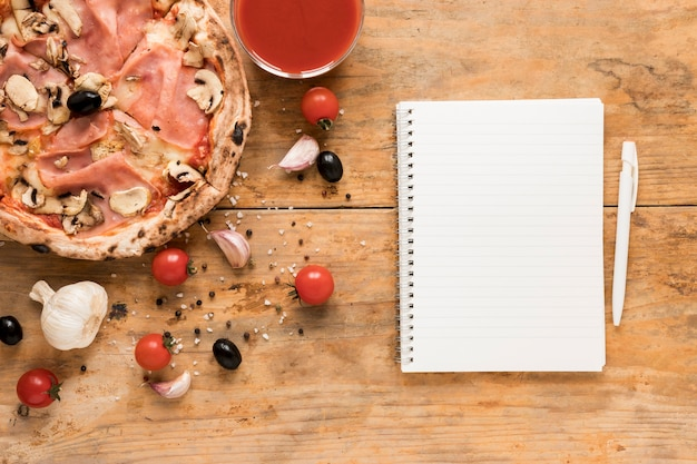 Leerer notizblock und stift nahe speckteigwaren mit tomatensauce auf holztisch Kostenlose Fotos