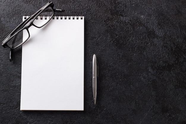 Leerer notizblockstift und -gläser auf dunklem hölzernem modernem bürotischspott herauf draufsicht Premium Fotos