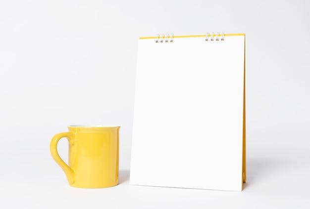 Leerer papierspiralenkalender und gelbe schale für modellschablone Premium Fotos