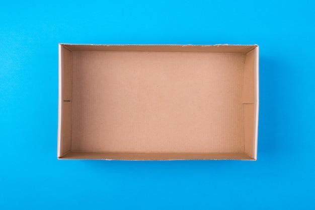 Leerer papppapierkasten auf blauem hintergrund. Premium Fotos