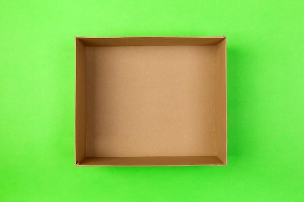 Leerer papppapierkasten auf grün. lieferkonzept, ansicht von oben Premium Fotos