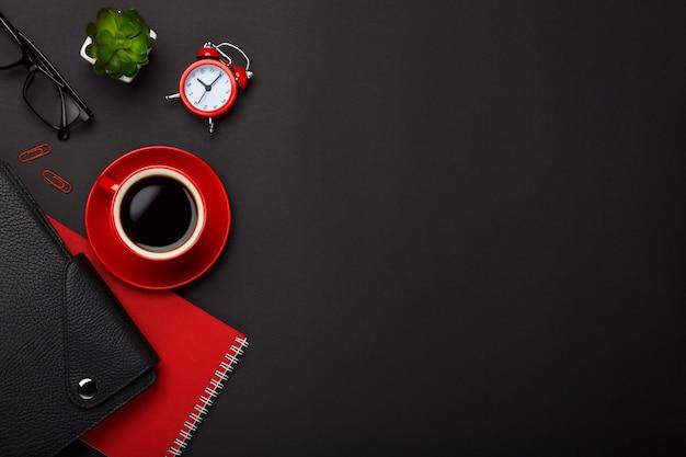 Leerer platzdesktop der schwarzen kaffeetasse-notizblockwecker-blumentagebuchgläser des hintergrundes roten Premium Fotos