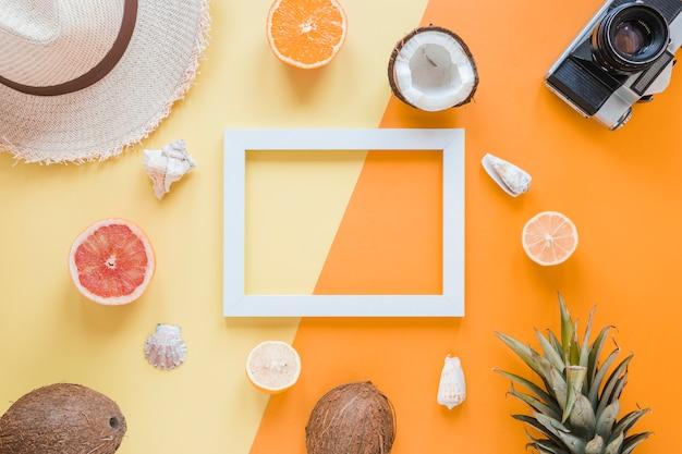 Leerer rahmen mit reisezubehör, früchten und muscheln Kostenlose Fotos