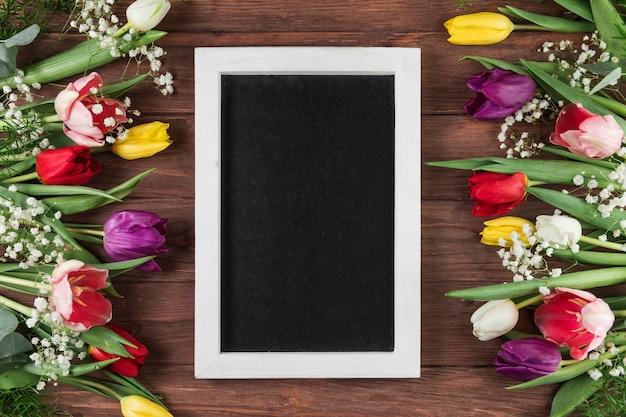Leerer rahmen mit weißer grenze zwischen den bunten tulpen und der atemblume des babys auf hölzernem schreibtisch Kostenlose Fotos