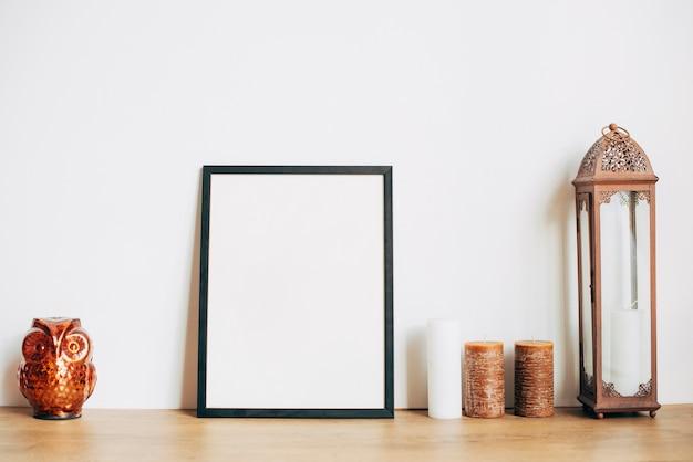Leerer rahmen nahe kerzen und eulenandenken Kostenlose Fotos