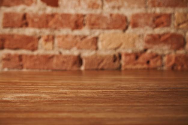 Leerer rustikaler brauner holztisch mit backsteinmauer hinten, hintergrund für stillleben und andere kompositionen Kostenlose Fotos