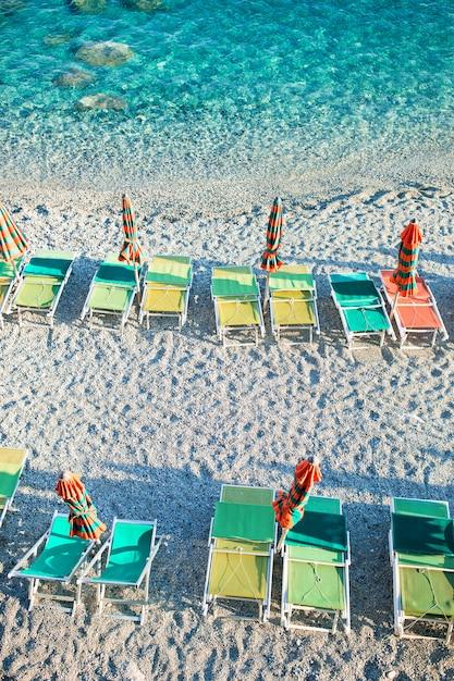Leerer strand mit geschlossenen regenschirmen auf italienischer küste Premium Fotos