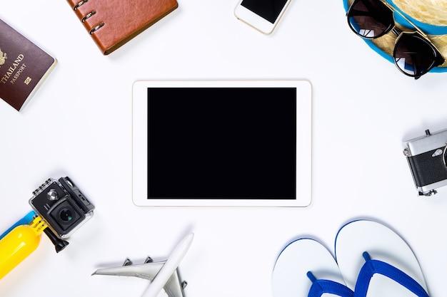 Leerer tablettenschirm, der durch reisegegenstände umgibt Premium Fotos