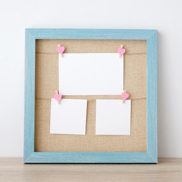 Leerer weißbuchnotizblock, der am blauen hölzernen rahmenhintergrund der weinlese hängt Premium Fotos