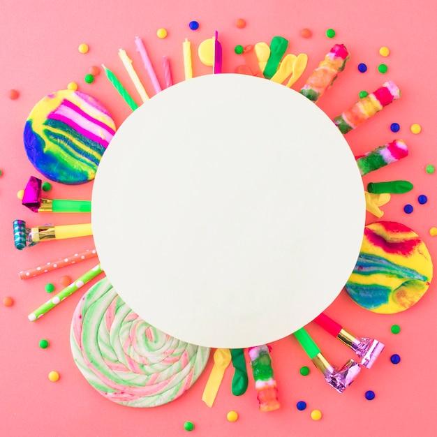 Leerer weißer rahmen über partyzubehör und -süßigkeiten auf rosa oberfläche Kostenlose Fotos