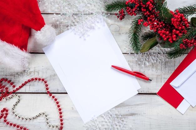 Leeres blatt papier auf holztisch mit einem stift und weihnachtsdekorationen Kostenlose Fotos