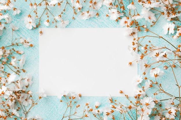Leeres blatt papier, umgeben von kleinen weißen blumen. Premium Fotos