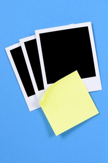 Leeres foto druckt mit gelber klebriger anmerkung auf einem blauen kraftpapierhintergrund. Premium Fotos