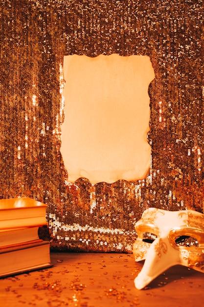 Leeres gebranntes papier auf glänzendem paillettengewebe und parteimaske auf schreibtisch Kostenlose Fotos