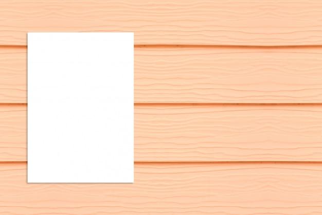 Leeres gefaltetes papierplakat, das an der hölzernen wand, schablonenspott hängt für das hinzufügen ihres designs. Premium Fotos