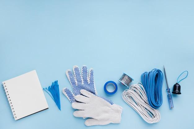Leeres gewundenes notizbuch und elektrikerausrüstung auf blauer oberfläche Kostenlose Fotos
