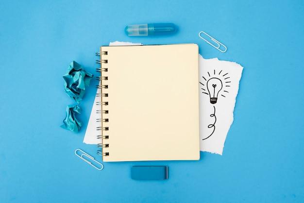 Leeres gewundenes tagebuch und briefpapierversorgungen mit hand gezeichneter glühlampe auf weißem kartenpapier über blauer oberfläche Kostenlose Fotos