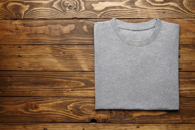 Leeres graues t-shirt genau gefaltet auf rustikaler holztischoberansicht Kostenlose Fotos