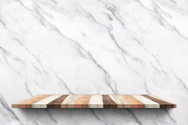 Leeres hölzernes plankenregal am weißen marmorwandhintergrund Premium Fotos