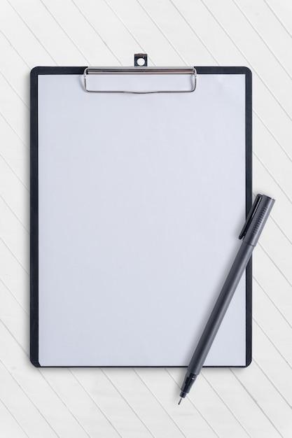 Leeres klemmbrett und stift auf weißer konkreter tabelle Premium Fotos