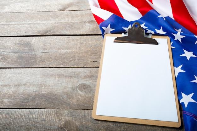 Leeres klemmbrett und usa-flagge auf hölzernem hintergrund Premium Fotos