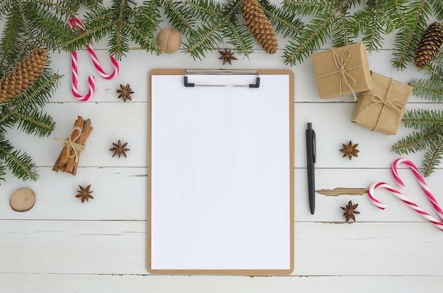 Leeres klemmbrett, weihnachtsdekoration auf weißem hölzernem hintergrund. flache lage, draufsicht Premium Fotos
