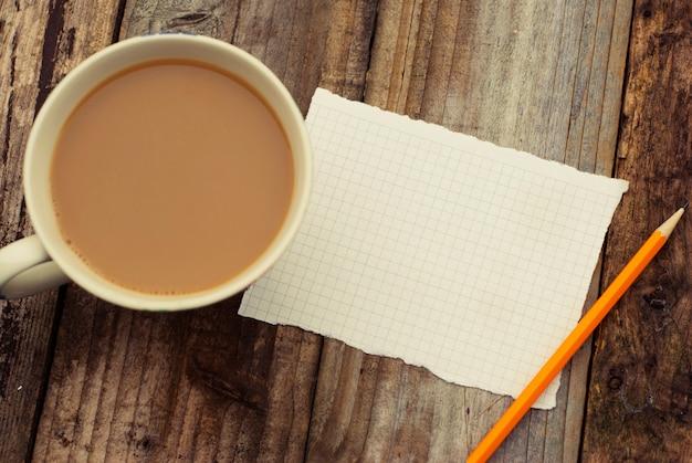 Leeres leerseitenpapier und -tasse kaffee auf holztisch. bereit zum hinzufügen von text. retro gefiltert. flach liegen. Premium Fotos