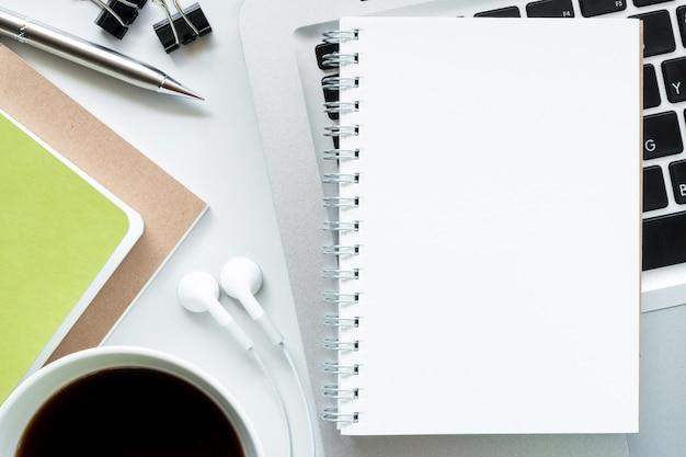 Leeres notizbuch auf moderne weiße schreibtischtabelle. draufsicht, flach zu legen. Premium Fotos