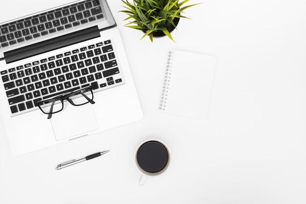 Leeres notizbuch ist auf weiße schreibtischtabelle mit laptop, kaffeetasse und büroartikel. draufsicht mit exemplar Premium Fotos