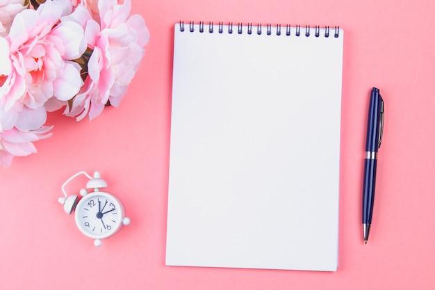 Leeres notizbuch mit blauem stift auf einem rosa pastellhintergrund. modell, rahmen, vorlage Premium Fotos