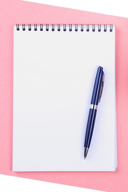 Leeres notizbuch mit blauem stift auf rosa pastellhintergrund. modell, rahmen, vorlage. Premium Fotos