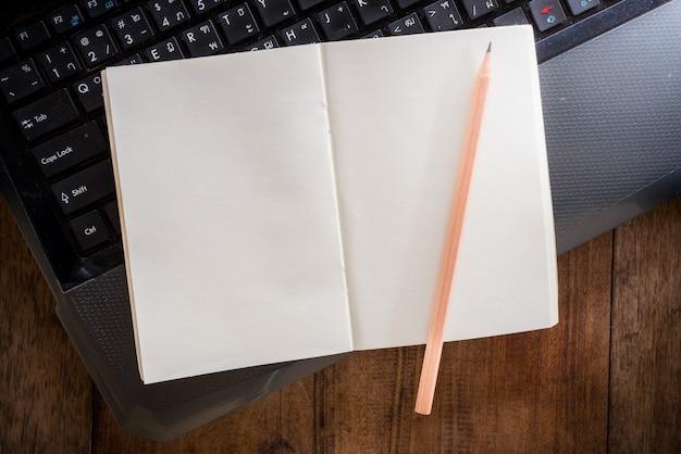 Leeres notizbuch mit bleistift auf laptop Premium Fotos