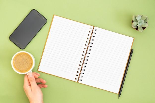 Leeres notizbuch mit der leeren seite, bleistift und hand, die eine kaffeetasse halten. tischplatte, arbeitsplatz auf grünem hintergrund. kreative flachlage. Premium Fotos
