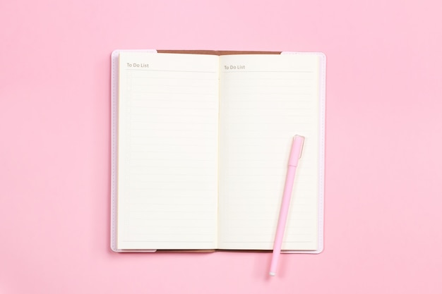 Leeres notizbuch mit stift auf rosa pastellschreibtisch Premium Fotos