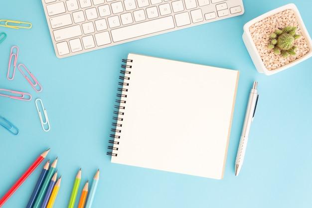 Leeres notizbuch mit tastatur und stift auf blau Premium Fotos