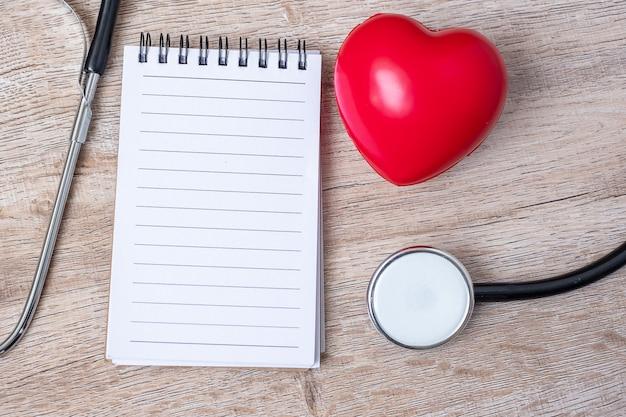 Leeres notizbuch, stethoskop mit roter herzform auf hölzernem hintergrund. Premium Fotos