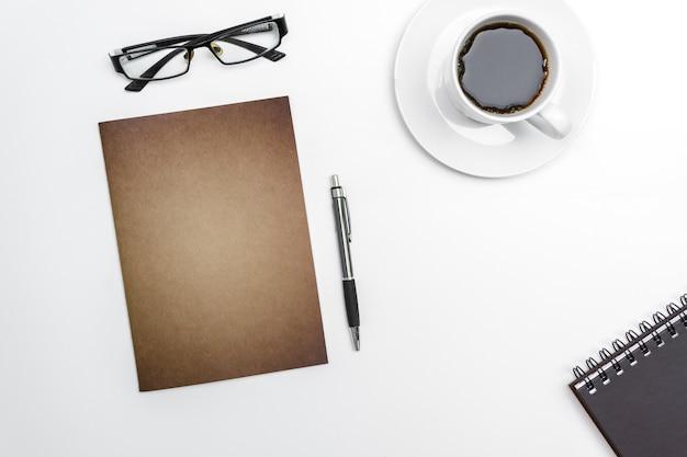 Leeres notizbuch, stift und gläser der draufsicht auf weißem schreibtischhintergrund. Premium Fotos
