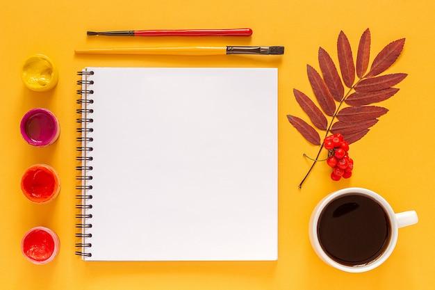 Leeres offenes einklebebuch, farbige blattherbarium- und -aquarellfarben, pinsel auf gelb. zurück zur schule Premium Fotos
