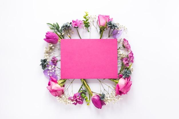Leeres papier auf verschiedenen blumen auf tabelle Kostenlose Fotos