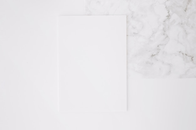 Leeres papier auf weißem schreibtischhintergrund Kostenlose Fotos