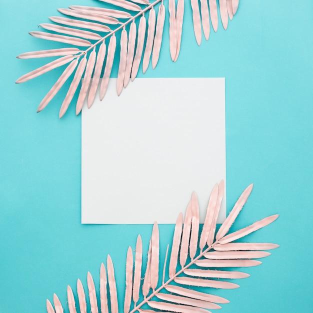 Leeres papier mit rosa blättern auf blauem hintergrund Kostenlose Fotos