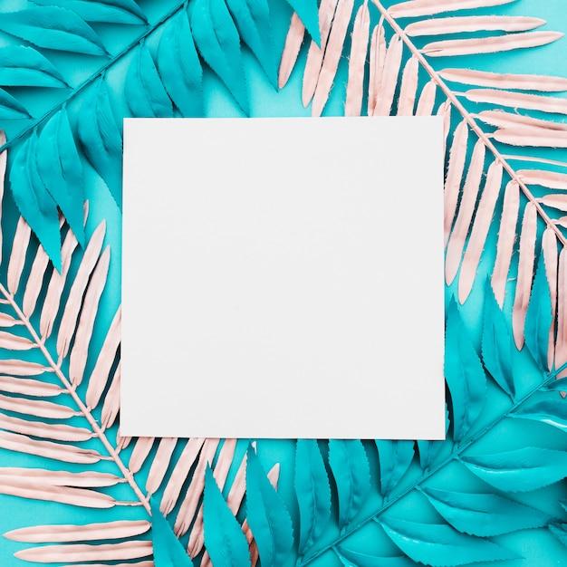 Leeres papier mit rosa und blauen palmblättern auf blauem hintergrund Kostenlose Fotos