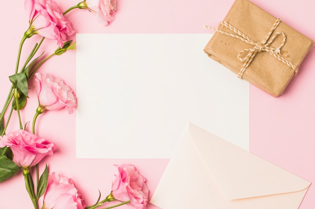 Leeres papier mit umschlag; frische rosa blume und braune eingewickelte geschenkbox über rosa hintergrund Kostenlose Fotos