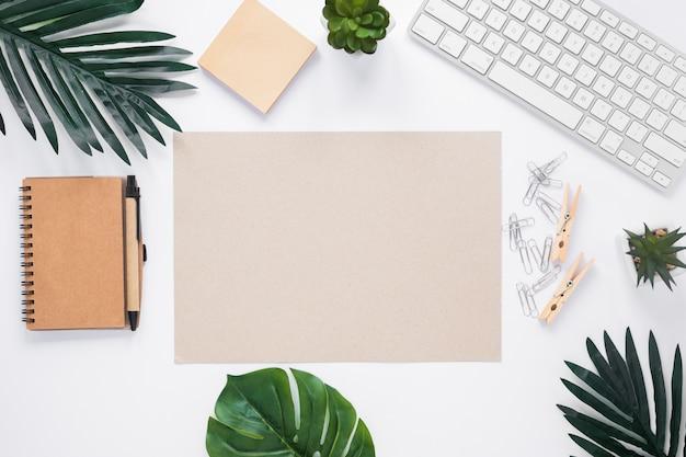 Leeres papier umgeben mit büroartikel auf weißem arbeitsplatz Kostenlose Fotos