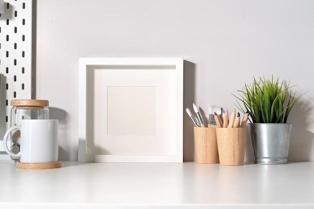 Leeres plakat des modells auf minimaler schreibtischtabelle Premium Fotos