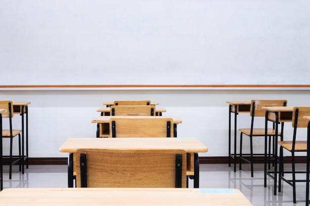 Leeres schulklassenzimmer mit schreibtischen stuhlholz, grünes brett und whiteboard in der highschool Premium Fotos