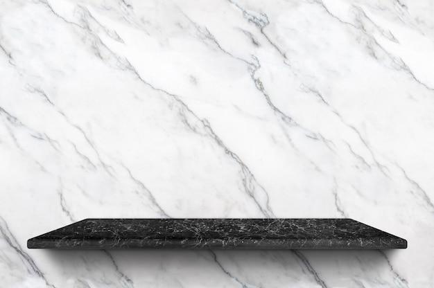 Leeres schwarzes marmorregal am weißen marmorwandhintergrund für anzeigenprodukt Premium Fotos