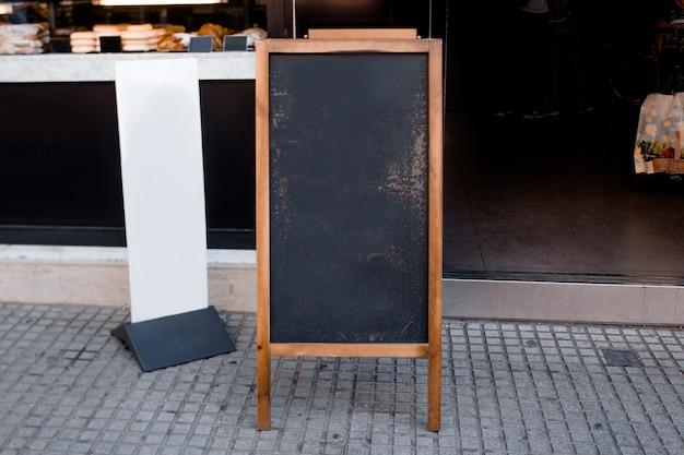 Leeres tafelmenü und weiße anschlagtafel vor dem restaurant an der straße Kostenlose Fotos